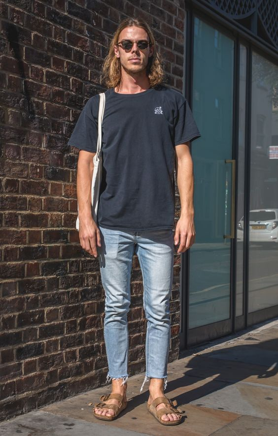 The model is pairing his Birkenstocks with a light blue jeans and a loose tee as well with a tote bag for a more casual hipster fit!
