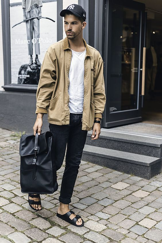 Here the has a more minimalistic look with a skinny/slim dark denim, a white t-shirt and a beige jacket. Paired with a bag.