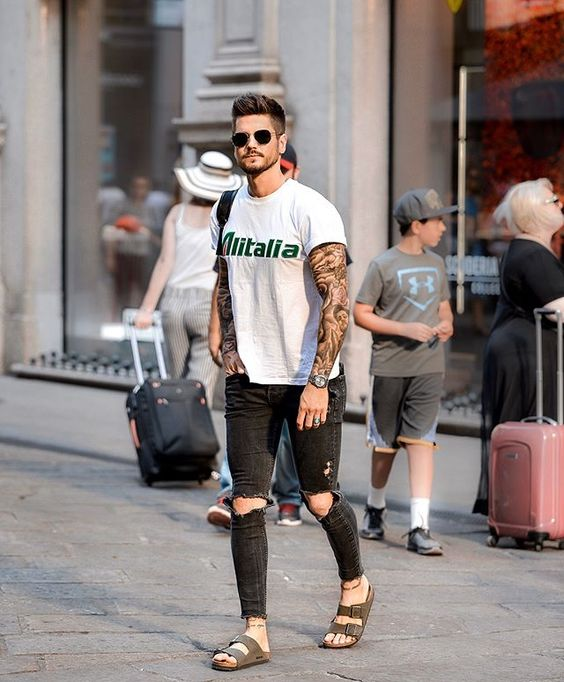 This model is styling his Birkenstocks with a ripped dark jeans and a muscle tee.